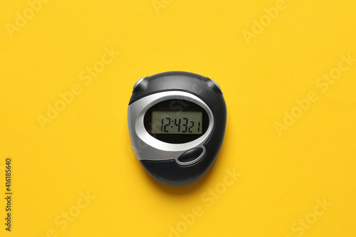 Canvas Print Modern stopwatch on yellow background, top view