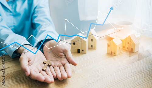 Fotografija Brown wooden cross on hand and illustration line chart for high level earnings property, with wooden house, concept of home church