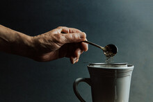 A Old Hand Preparing A Tea Over A Dark Background With Copy Space And Dark Tones