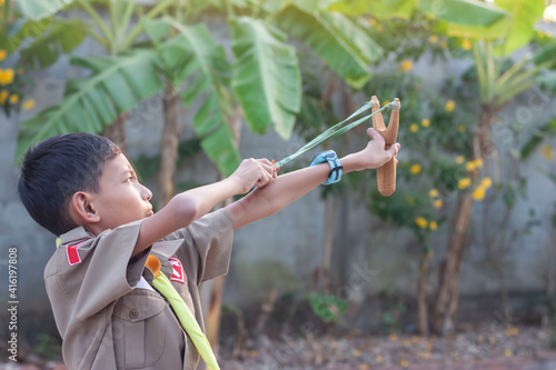 Foto Asian boy holding and playing shooting wooden catapults in the morning