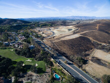 A Charred Hillside Remains From A Wildfire With A Golf Course That Survived Across The Road