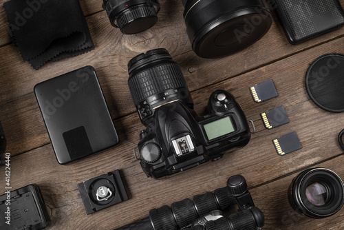 Obraz A set of camera and photographic equipment (lens, tripod, filter, memory card, hard disk) on a wood table. Professional photographer accessories background. - fototapety do salonu