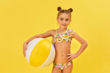 Cute Little Child Girl In Swimwear With Beach Ball On Yellow Background