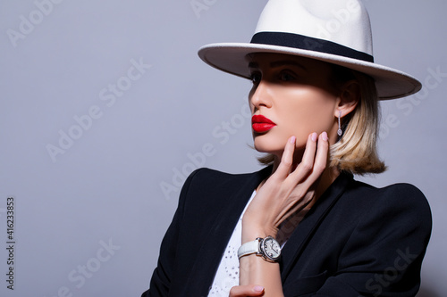 Fashionable and stylish woman in trendy jewelry with stones and diamond watches. elegant model in white hat, red lips makeup. Fashion look, beauty and style. Gray background