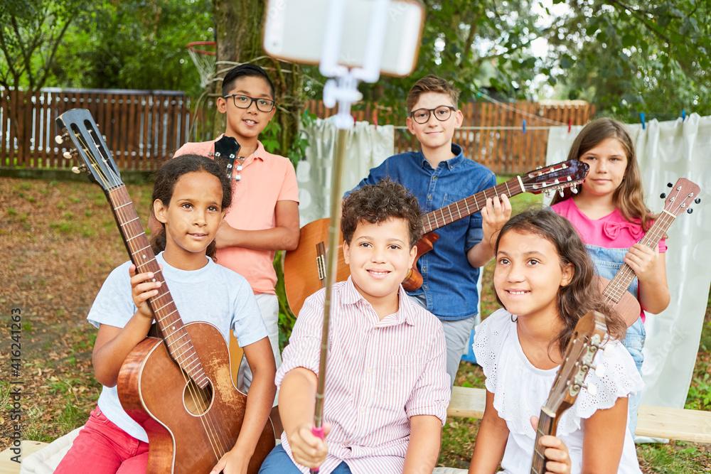 Fototapeta Children as a music band take selfie at summer camp