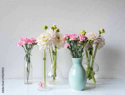Close up of pink carnations and white dahlia flowers in glass and ceramic vases Fototapet