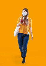 Girl Is Walking, Wearing Casual Style With Bag And Listening Music, Pandemic And Mask On The Face, Looking Cell Phone Isolated.