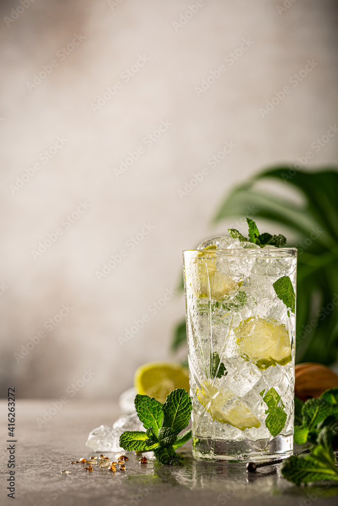Fototapeta Mojito cocktail with lime and mint in highball glass on a grey background. Summer cold beverages concept with copy space