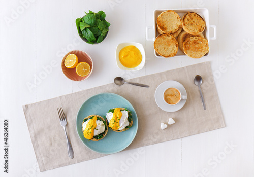 Fotografie, Tablou Eggs Florentine, English muffins, spinach, poached eggs, Mornay sauce, chive herbs, lemon, cup of coffee