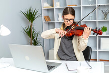 Girl Student Learns To Play The Violin Online Using A Laptop.