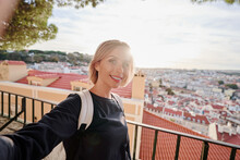 Traveling By Portugal. Young Traveling Woman Taking Selfie In Old Town Lisbon With View On Red Tiled Roofs, Ancient Architecture.