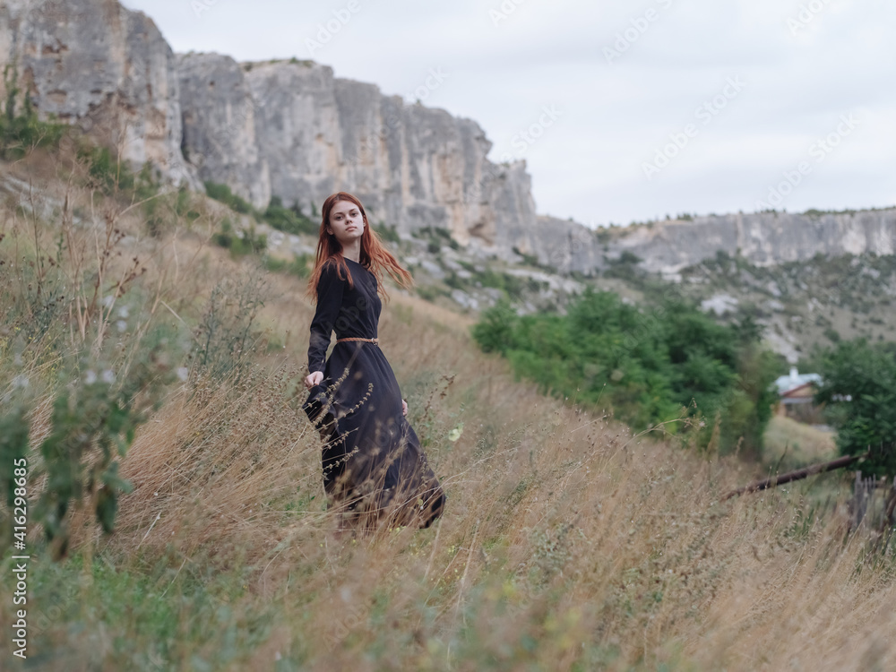 Fototapeta woman traveler in a black dress runs on dry grass in the meadow and mountains in the background
