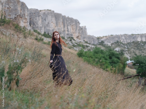 Fototapeta woman traveler in a black dress runs on dry grass in the meadow and mountains in the background obraz