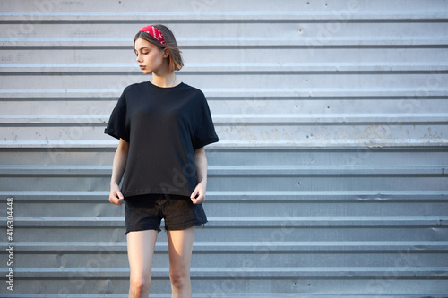 Fototapeta Woman wearing black blank t-shirt with space for your logo, mock up or design in casual urban style obraz