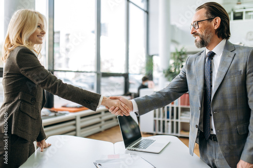 Confident influential coworkers shaking hands on business meeting, starting negotiations. Successful middle aged colleagues coming to agreement, sign an important contract
