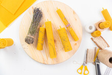 Yellow Candles Made From Natural Beeswax With Lavender On White Background, Top View. Production Concept DIY