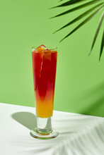 Strawberry And Peach Lemonade Drink Over Green Background. White Table With Sunshine And Palm Leaf Shadow Still Life. Summer, Fresh, Healthy And Tropic Concept