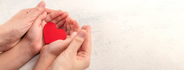 Children and mothers hands holding red heart on white textured background. Concept of health care, love, organ donation, mindfulness, wellbeing, family insurance