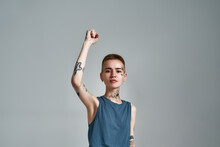 Cute Tattooed Young Caucasian Woman Protester With Piercing Looking At Camera While Posing With Raised Arm Isolated Over Gray Background