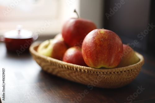Obraz Jabłka czerwone w wiklinowym koszyku na drewnianym stole ciemnym - fototapety do salonu