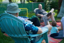 Two Men Sitting Across From Each Other In Adirondack Chairs In Backyard; Socially Distant Entertaining And Socializing