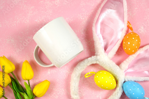 Fototapeta Easter product mockup with bunny ears and easter eggs on pink background flatlay. White coffee mug mock up with negative copy space for your text or design here. obraz
