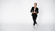 Elegant Ballerina In Suit And Pointe Shoes Holding Coffee To Go While Walking On White