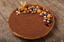 Chocolate Tart Decorated With Fresh Berries And Cape Gooseberry On Wooden Table