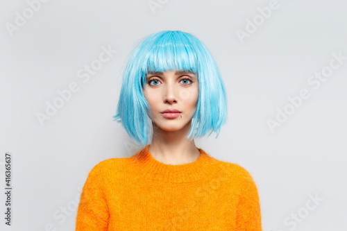 Studio portrait of pretty young girl with blue bob hairstyle in orange sweater on white background Fotobehang