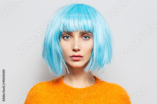 Canvas Close-up studio portrait of confident young girl with blue bob hairstyle in orange sweater on white background