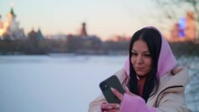 Brunette In Hoodie Makes Selfie On Shore Of Ice Covered Pond In The City Park. Cold Winter Day.