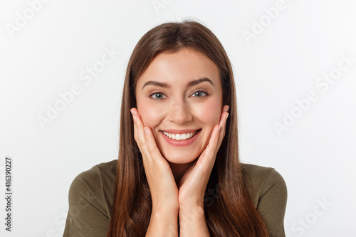 Close-up portrait of surprised beautiful girl holding her head in amazement and open-mouthed. Over white background © Mix and Match Studio