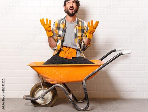 Foto young bearded construction worker man on a wheelbarrow