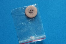 One Plastic Brown Button In A Bag Lies On A Blue Table