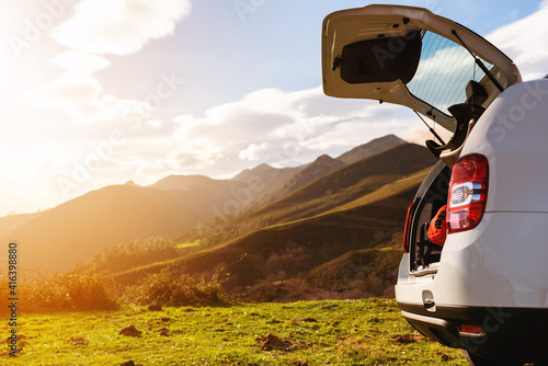 Fotografie, Obraz Open off-road car trunk with luggage inside on a mountain at sunset