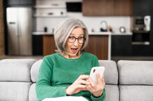 Surprised Senior Woman Looking At The Phone Screen Sitting On The Coach At Home, An Wondered Elderly Lady Saw Unexpected Good News Or Received Pleasantly Message, Sales Proposal On The Smartphone
