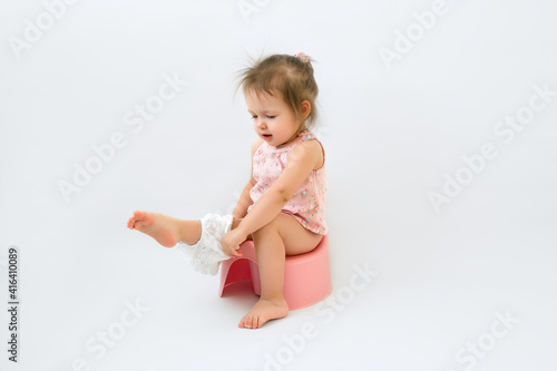Canvas Print The child sits on the potty and puts on her panties