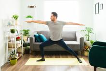 Hispanic Man Practicing A Warrior 2 Yoga Pose At Home