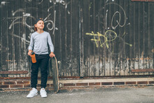 Teenager Skateboarder Boy Standing Beside A Wooden Grunge Graffiti Wall With Skateboard And Water Bottle Flask. Youth Generation Freetime Spending And Active People Concept Image.