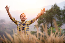 Boy Arms Raised To Pray And Worship God In The Meadow In The Evening Sunset. Young Christian Concept.