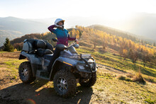 Young Happy Woman In Protective Helmet Enjoying Extreme Ride On Atv Quad Motorbike In Autumn Mountains At Sunset.