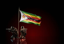 Concept Of Military Conflict. Waving National Flag Of Zimbabwe. Two Soldier Statue Guards Defending The Symbol Of Country Against Red Wall