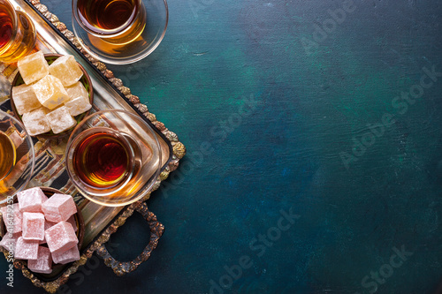 Fotografia Tea in traditional glass cups  and  turkish delight  on dark blue-green painted wooden background  with empty space for text