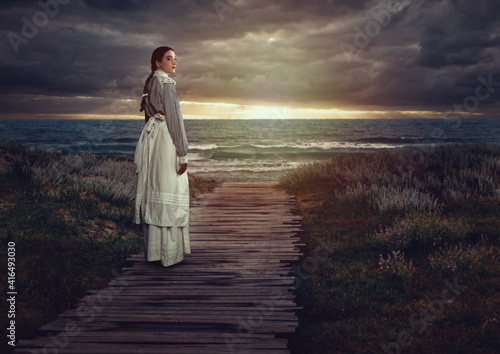 Fototapeta Young victorian girl in white dress and blue striped blouse on a boardwalk at the coast at sunset. obraz