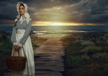 Victorian Girl With Hood And Wicker Basket In White Dress And Blue Striped Blouse On The Coast At Sunset.