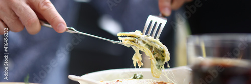 Fotografia Bistro visitor sitting at table holding fork and knife with piece of bolognese