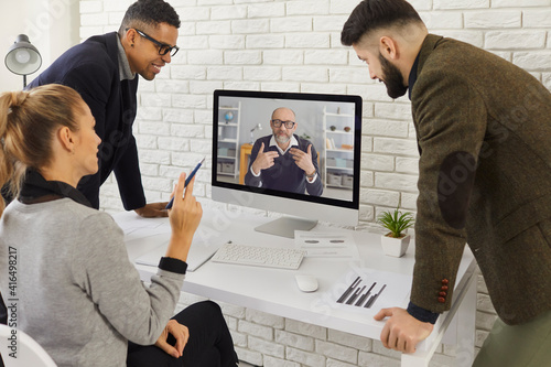 Canvas Print Multiracial business team looking at computer, video calling senior colleague, group mentor or CEO and having online discussion