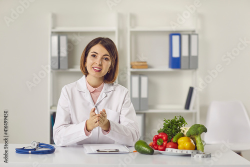 Fototapeta Female nutritionist provides patients with online consultations while sitting in her office. Woman sitting in front of a webcam and talking in a video chat. Concept of proper nutrition. obraz