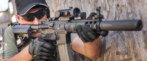 Fotografering Military army soldier in action tactical combat shooting from rifle machine gun