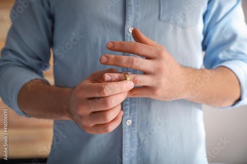 Man taking off wedding ring on blurred background, closeup Fototapete